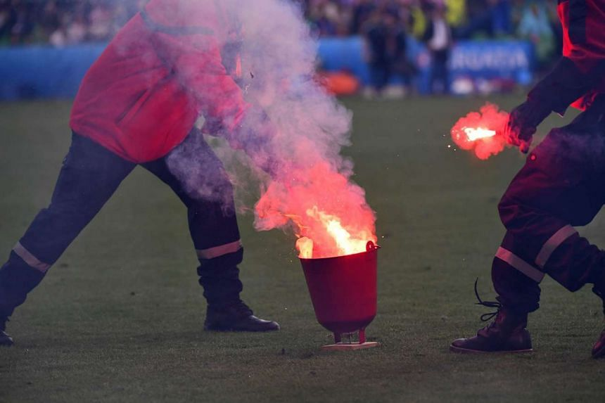 Firefighters extinguish flares lobed onto the pitch during the Euro 2016 group D football match between Czech Republic and Croatia at the Geoffroy-Guichard stadium in Saint-Etienne on June 17, 2016.