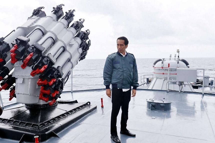Indonesian President Joko Widodo stands on the deck of the warship KRI Imam Bonjol during a visit to the Natuna Islands on June 23, 2016.