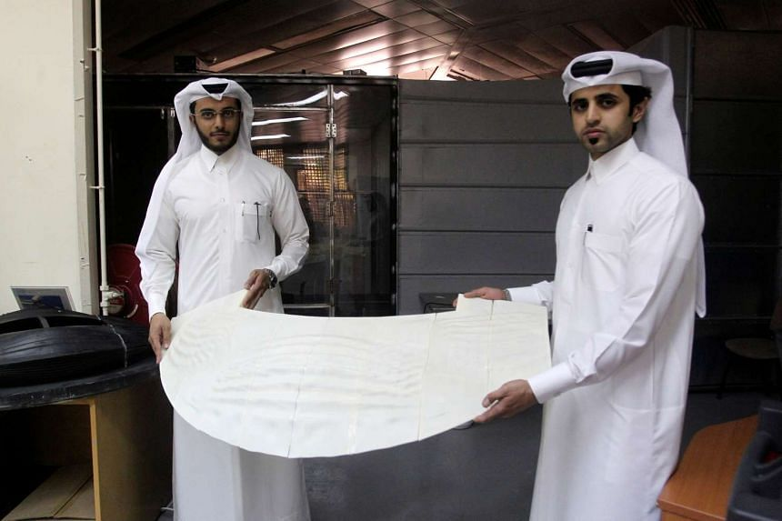 Mechanical engineers Abdullah Mojeb Aldar (left), 26, and Fahad al-Musalam, 24, hold up a panel of a 3D printed World Cup stadium model as it is tested at a laboratory at Qatar University in Doha, Qatar on June 16, 2016.