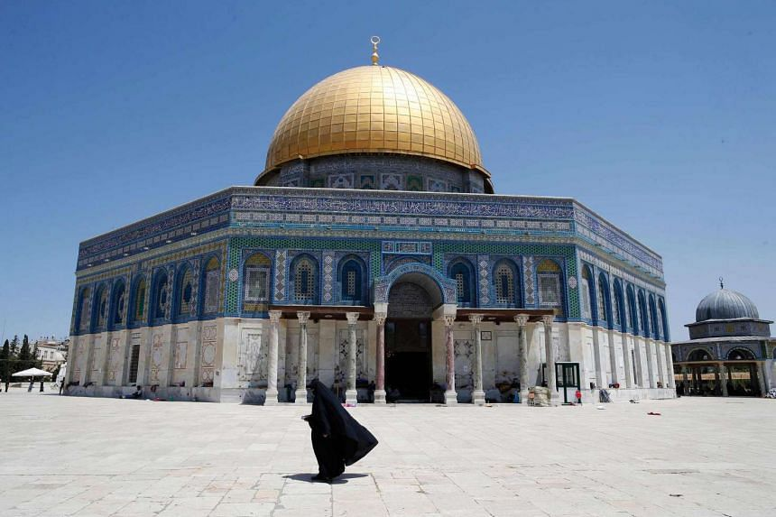 A Palestinian woman walks past the Dome of the Rock in Al-Aqsa Mosque compound in Jerusalem's Old City, on June 26, 2016.