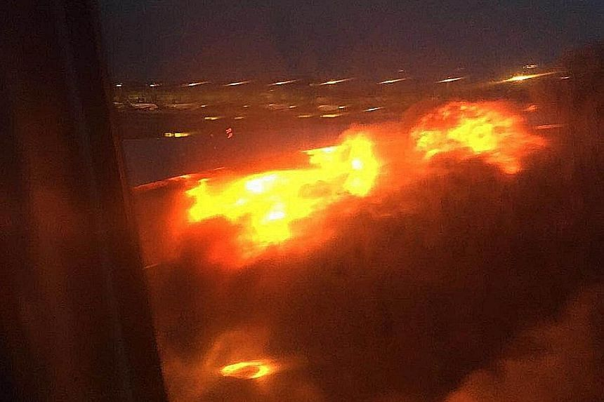 """Above: The blackened wing of Flight SQ368 after the fire was put out. None of the passengers and crew were hurt. Left: The blaze was quite fierce, said passenger Lee Bee Yee. """"The SQ crew were very professional in calming everyone down."""""""