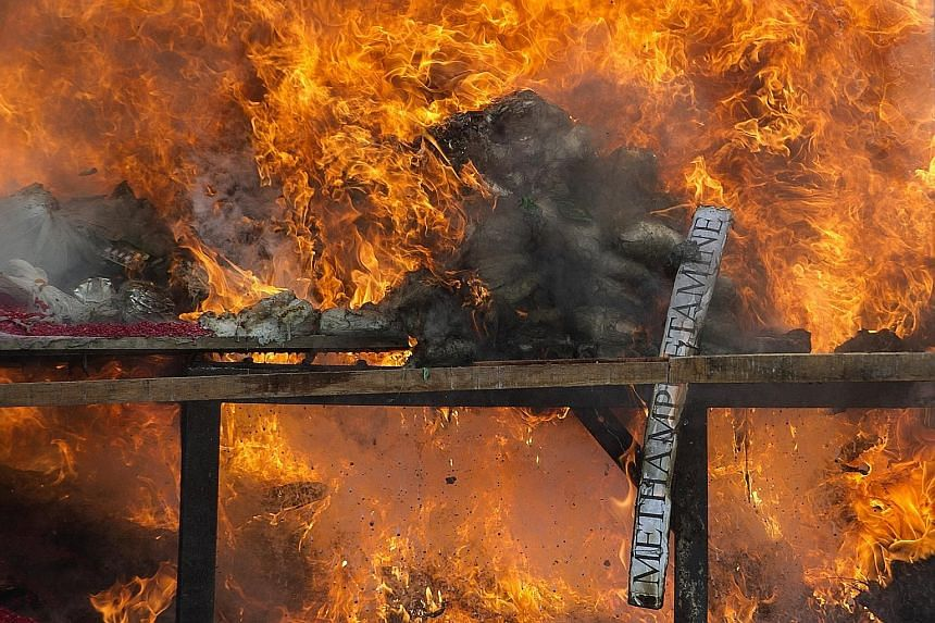"A pile of seized drugs being burned during a ceremony to mark the United Nations' ""International Day against Drug Abuse and Illicit Trafficking"" in Yangon on Sunday. The Myanmar authorities destroyed narcotics worth US$56.3 million (S$76.4 million) o"