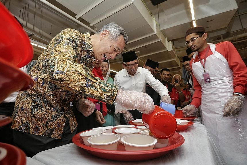PM Lee and Dr Yaacob pouring out porridge for the iftar at Al-Islah Mosque yesterday. About 350 community and religious leaders, mosque volunteers, and foreign workers who work nearby gathered to break fast with them.