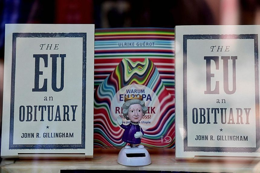 A figurine depicting Britain's Queen Elizabeth standing between copies of the book The EU An Obituary by John R. Gillingham, in a bookshop window in Berlin.