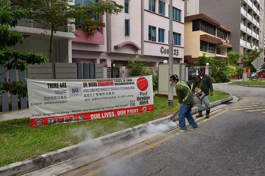 Workers conducting fogging operations in front of a dengue alert banner in Geylang.