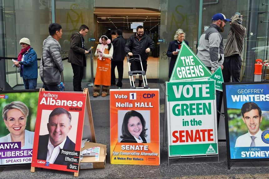 People handing out how-to-vote pamphlets behind political placards outside a polling station in Sydney's central business district on June 27, 2016.