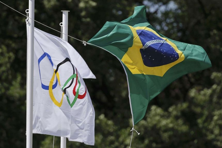 The Olympic and Brazilian flags fly over the site of ancient Olympia during the Olympic flame lighting ceremony for the Rio 2016 Olympic Games in Greece on April 21, 2016.