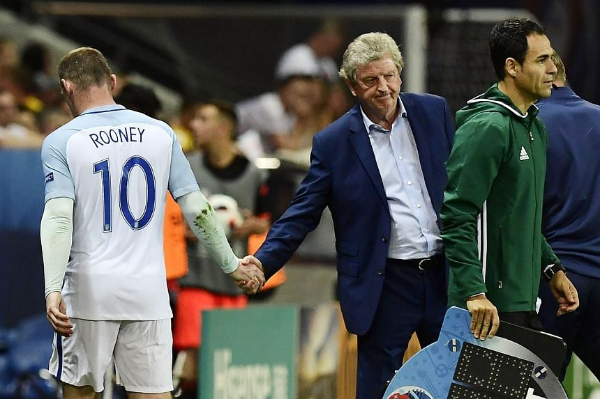 Wayne Rooney shakes hands with Roy Hodgson as he is substituted during the Euro 2016 round of 16 football match between England and Iceland.
