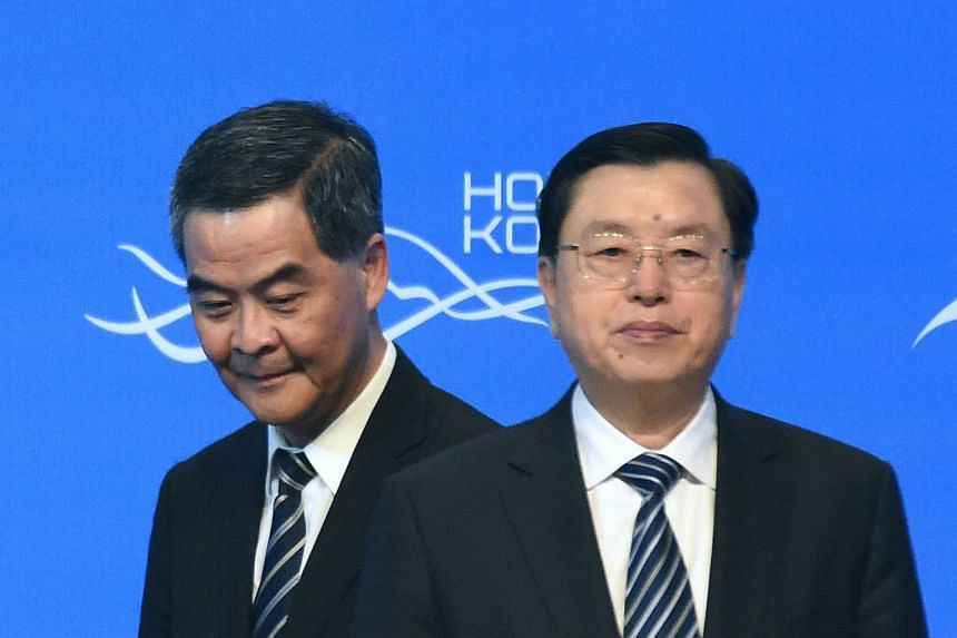 Hong Kong Chief Executive Leung Chun-ying (left) walks past Zhang Dejiang, while on stage as they open the Belt and Road Summit in Hong Kong.