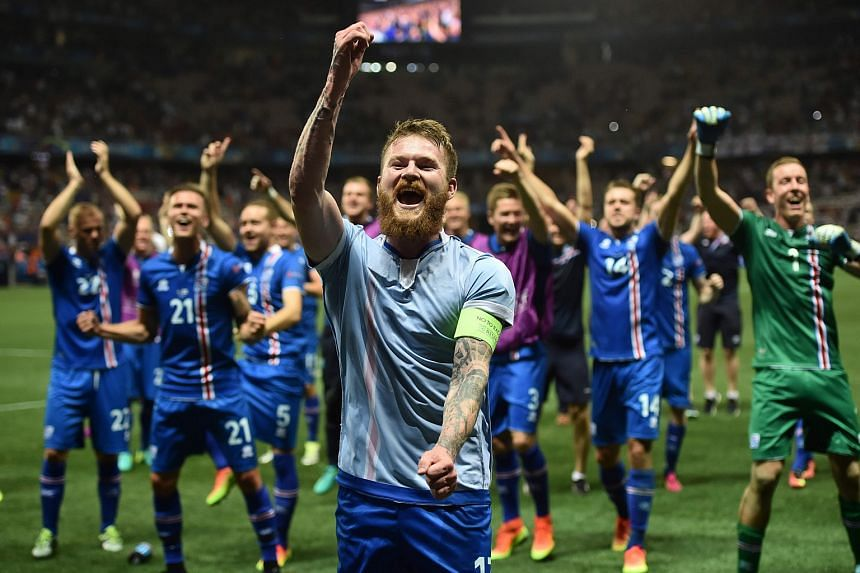 Iceland's midfielder Aron Gunnarsson and team mates celebrate after winning the Euro 2016 round of 16 football match between England and Iceland.