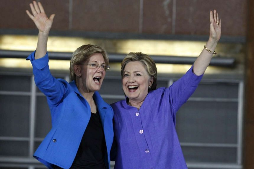 Democratic Presidential candidate Hillary Clinton (right) and US Senator Elizabeth Warren wave to the crowd before a campaign rally on June 27, 2016, in Cincinnati, Ohio.