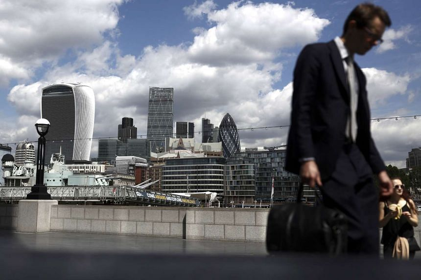 A pedestrian passes by the London skyline on June 28, 2016.