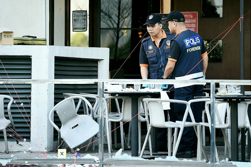 Malaysian forensic experts inspect the site of grenade attack at a restaurrant in Puchong district outside of Kuala Lumpur on June 28.