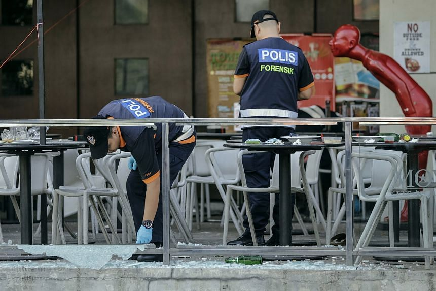 Malaysian police officers of the forensic department investigate the scene of a bomb explosion in Puchong, Selangor, near Kuala Lumpur, Malaysia on June 28.