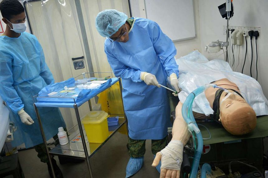 Medical Officer Dr Mizan Marican (right) simulates a chest tube insertion on a smart mannequin in the surgical high dependency unit of the Combat Support Hospital in Nee Soon Camp.