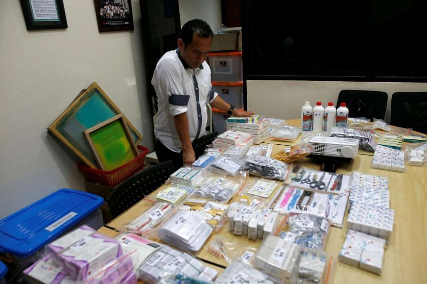 An officer from the National Police Criminal Investigation department looks at evidence confiscated from raids linked to fake vaccines production and distribution at the national police headquarters in Jakarta on June 27, 2016.