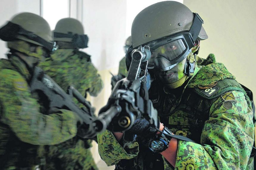 Soldiers of the 1st Commando Battalion doing a simulation of storming the building and clearing rooms at the Commando Training Institute in Pasir Ris Camp.