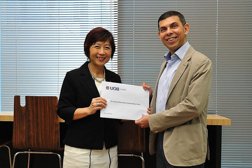 UOB's Ms Rosalind Lee presenting a cheque for the donation to ST editor Warren Fernandez yesterday.