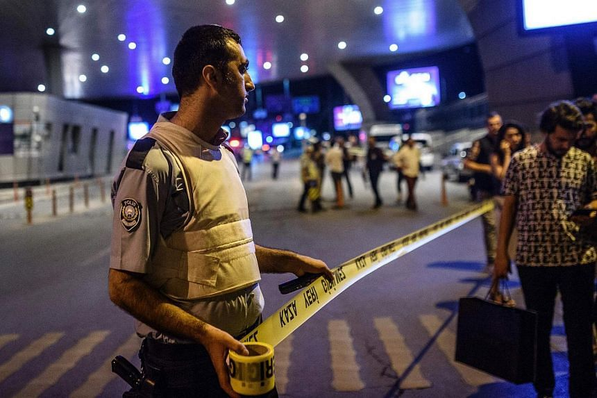 A policeman sets up a security perimeter as people leave the airport after two explosions followed by gunfire hit the Ataturk airport in Istanbul, Turkey on June 28.