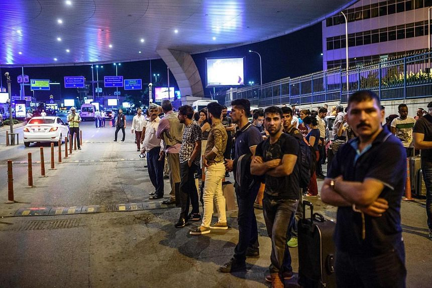 People standing outside the entrance after two explosions followed by gunfire hit Ataturk airport in Istanbul, Turkey.