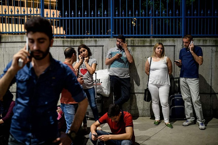 Passengers wait with their luggage outside the Ataturk airport in Istanbul after two explosions followed by gunfire hit the Turkey's biggest airport.