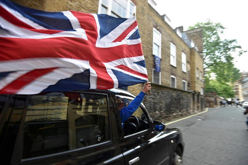 A taxi driver holds a Union flag, as he celebrates following the result of the EU referendum, in central London, Britain on June 24, 2016.