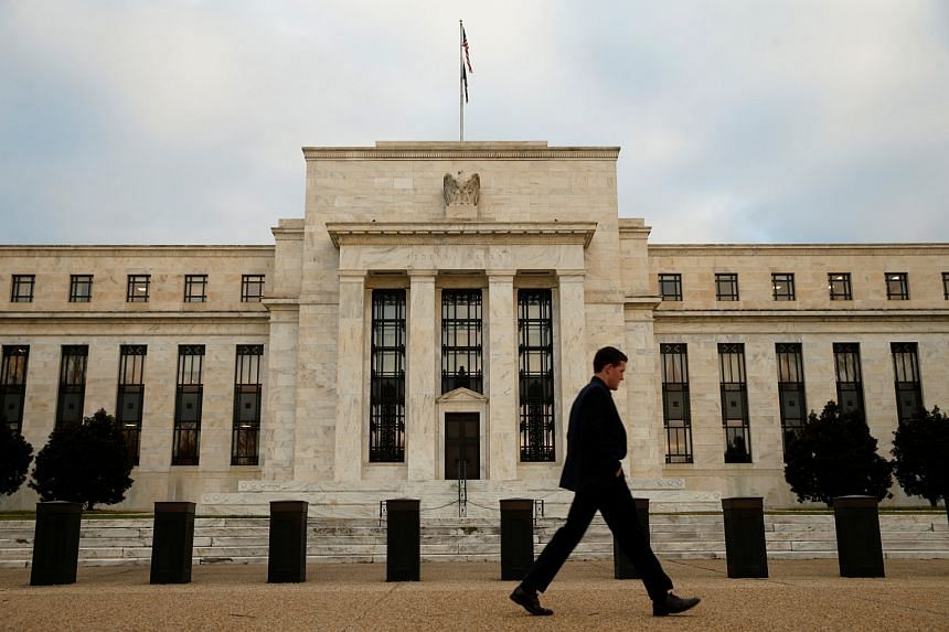 A man walks past the Federal Reserve in Washington.