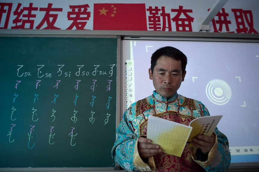 Mr Shi Junguang, a teacher in a village primary school in Sanjiazi, in the north-eastern Heilongjiang province, dressed in a red and turquoise robe with gold sleeves, which is reminiscent of the Manchus' traditional apparel. On the blackboard next to him