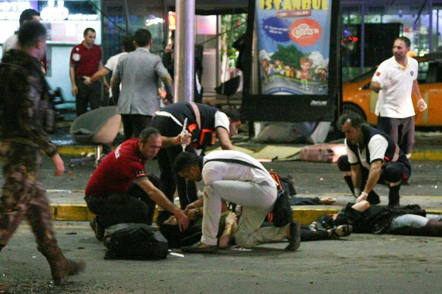 Paramedics attend to casualties injured outside Turkey's Ataturk airport following an attack, on June 28, 2016.