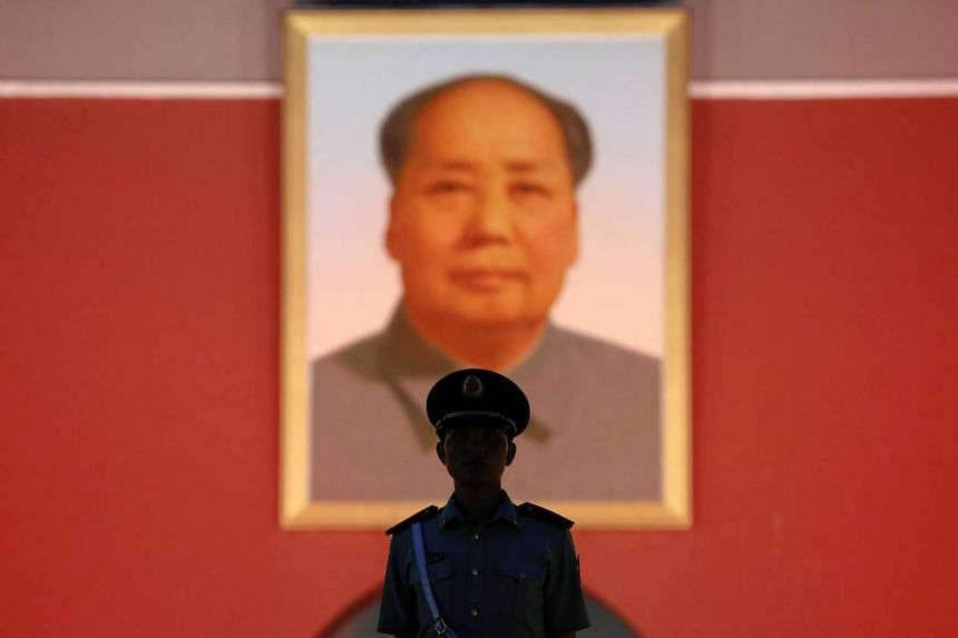 A paramilitary policeman stands guard under a giant portrait of late Chinese Chairman Mao Zedong at the Tiananmen gate in Beijing on June 3, 2016.