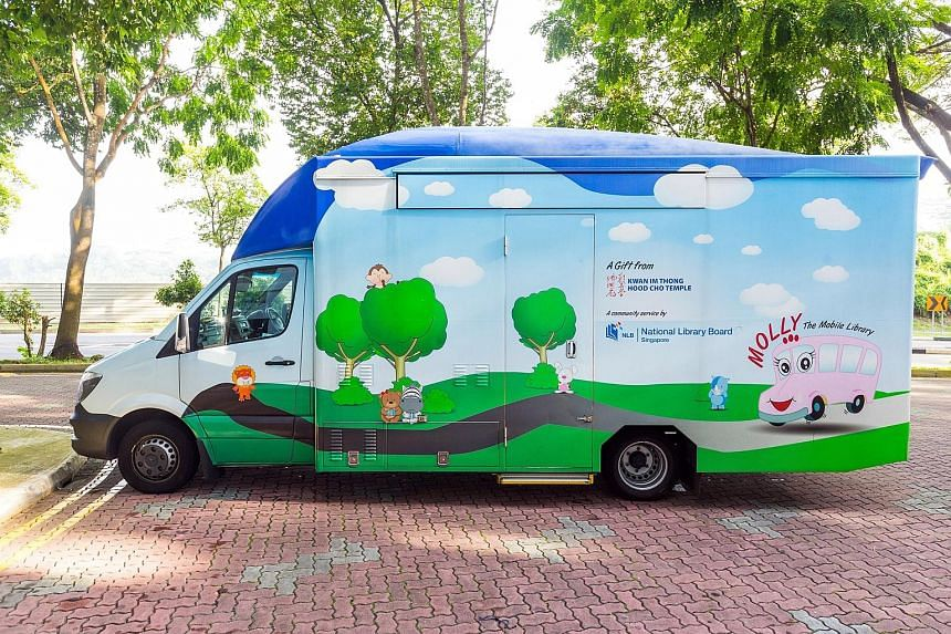 """(Clockwise from right) Children enjoying a book on the NLB's """"mini-Molly"""", one of two mini mobile libraries that will be open to the public at Bishan-Ang Mo Kio Park and East Coast Park on Saturday."""