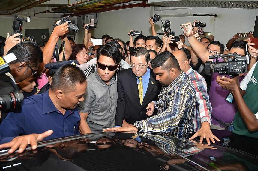 Penang Chief Minister Lim Guan Eng being led away by Malaysian Anti-Corruption Commission officials and plainclothes policemen yesterday. The DAP leader, who denies the graft accusations, was taken to the MACC office in Penang for an arrest warrant t