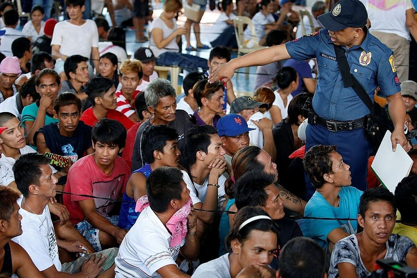A policeman talking to residents, who admitted to being drug users, at a police camp, after more than 700 people gave themselves up to policemen and local government officials in Quezon city, the Philippines, last Friday.
