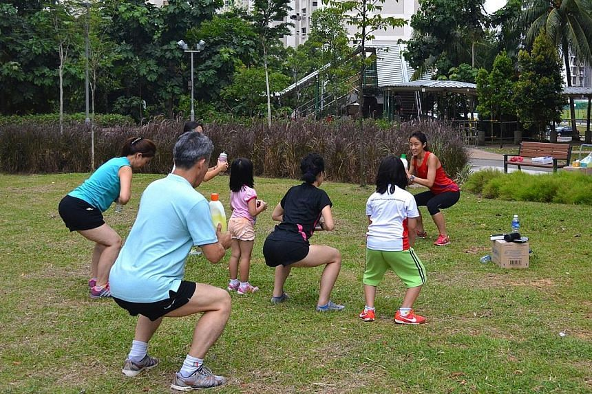 Led by Miss Shereen Ng, Clementi residents do squats using household items such as detergent bottles at Firefly Park in Clementi.