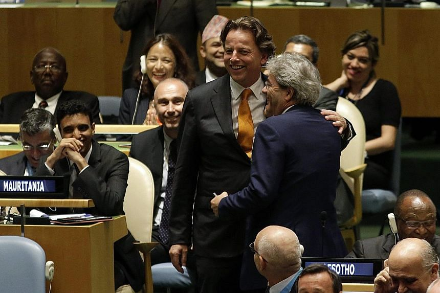 Dutch Foreign Minister Bert Koenders (wearing yellow tie) greeting his Italian counterpart Paolo Gentiloni at the UN headquarters in New York on Tuesday. Under an agreement which will be put to a vote, Italy will serve on the council next year, follo