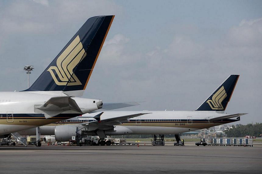 Two Singapore Airlines aircraft parked at the terminal in Changi Airport.
