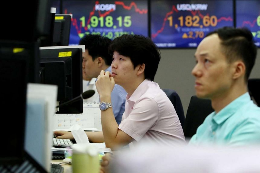 Foreign currency dealers work in front of electronic boards in Seoul, South Korea, on June 27.
