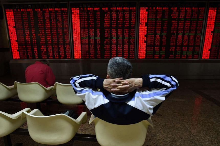 An investor watches stock price movements at a securities company in Beijing on June 15.