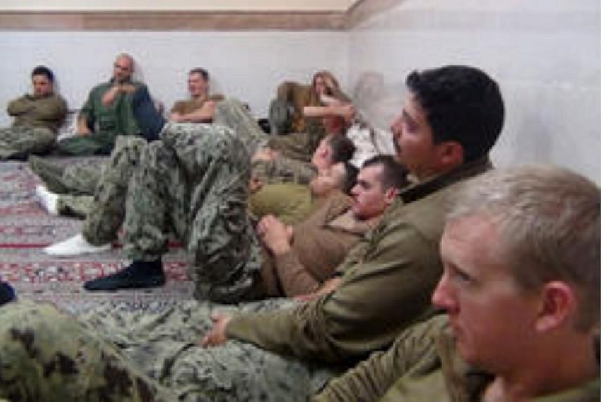 An undated picture released by Iran's Revolutionary Guards website shows American sailors sitting in an unknown place in Iran.