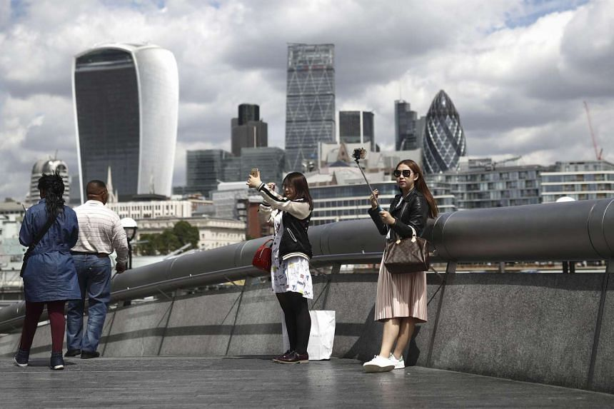 Tourists take photos with the London skyline as backdrop on June 28.