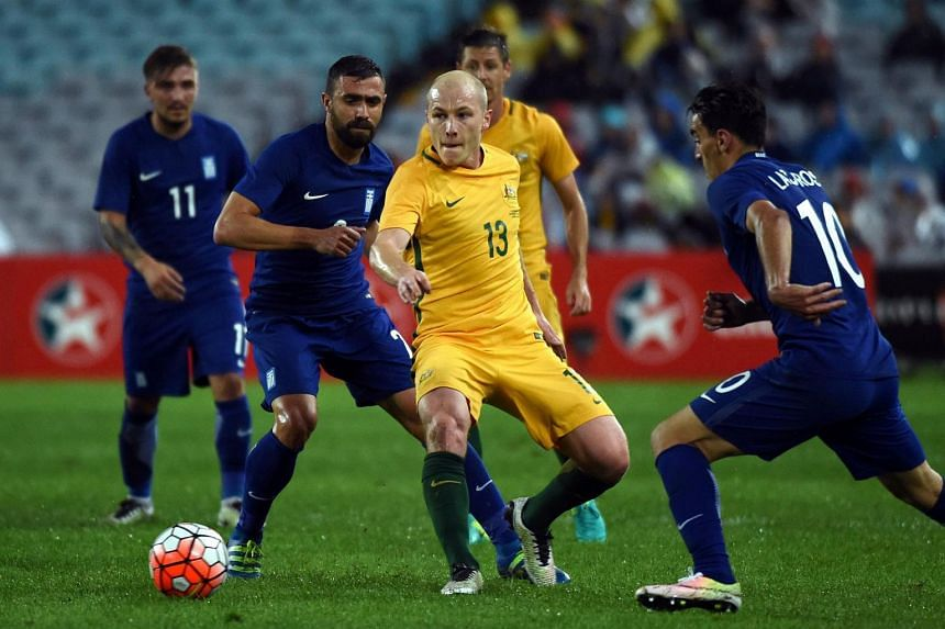 Australia's Aaron Mooy (centre) is tackled by Lazaros Christodoulopoulos of Greece (right) during their international football friendly match played in Sydney.