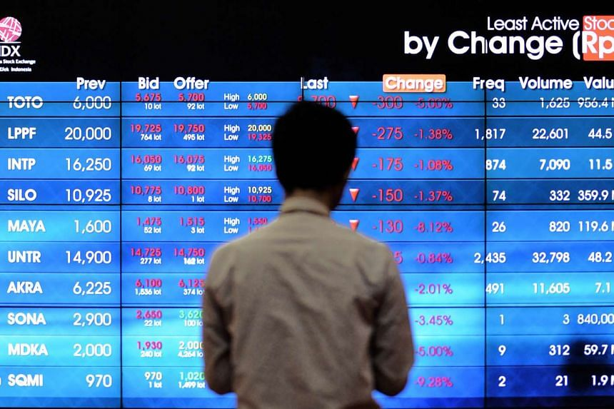 An Indonesian man looks at the stock exchange share prices board in Jakarta on June 28, 2016.