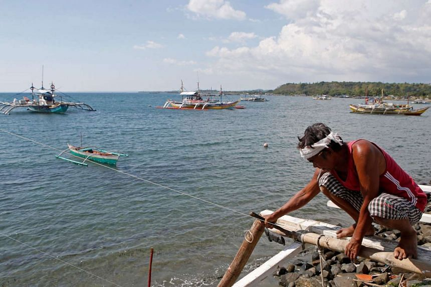 A fisherman repairs his boat overlooking fishing boats in the disputed Scarborough Shoal in the South China Sea, in the Philippines, on April 22, 2015.