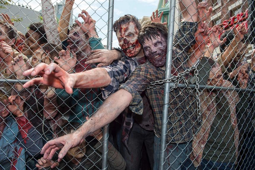 Actors dressed as zombies at the opening of theme park Universal Studios Hollywood's latest attraction, The Walking Dead, based on the television show, in California on Tuesday. The walk-through scare ride begins in a hospital setting and takes vis