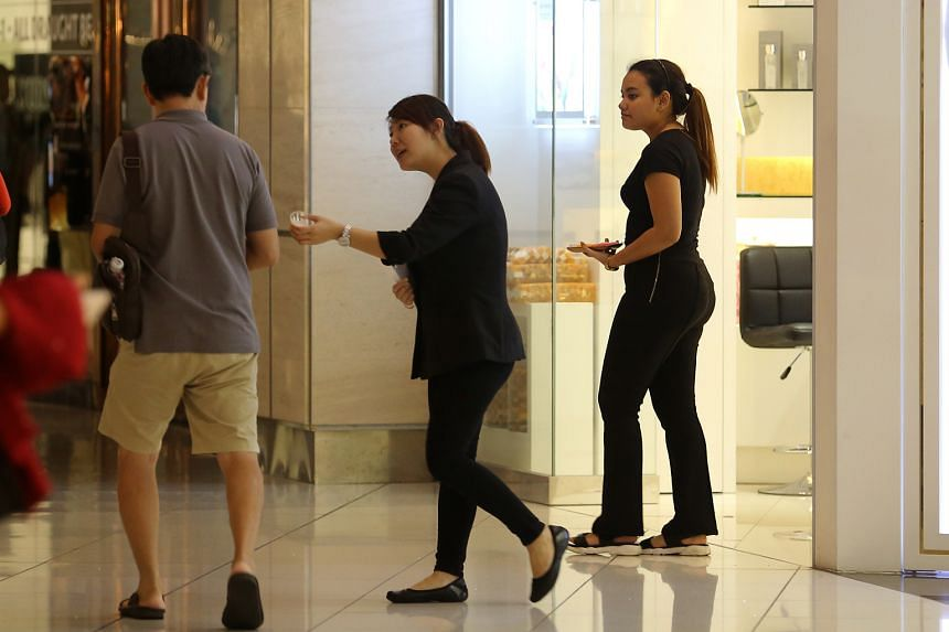 A salesperson from Dead Sea Premier at Suntec City offering free samples to a passer-by.