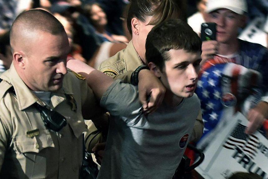 Police lead Michael Steven Sandford from Donald Trump's campaign rally in Las Vegas, Nevada, on June 18.
