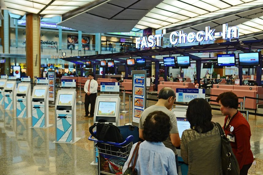 Passengers use the self-service check-in kiosks at Singapore Airlines (SIA) and SilkAir's check-in rows at Changi Airport Terminal 2.