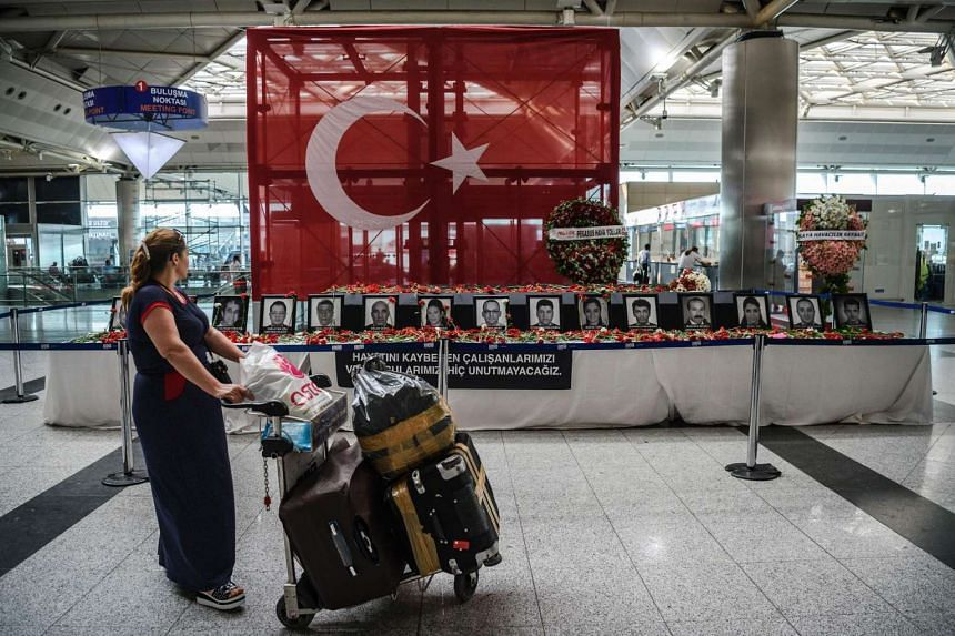 A passenger looks at the pictures of airport employees who died in the triple suicide bombing and gun attack that happened at Istanbul's Ataturk airport on Tuesday (June 28).