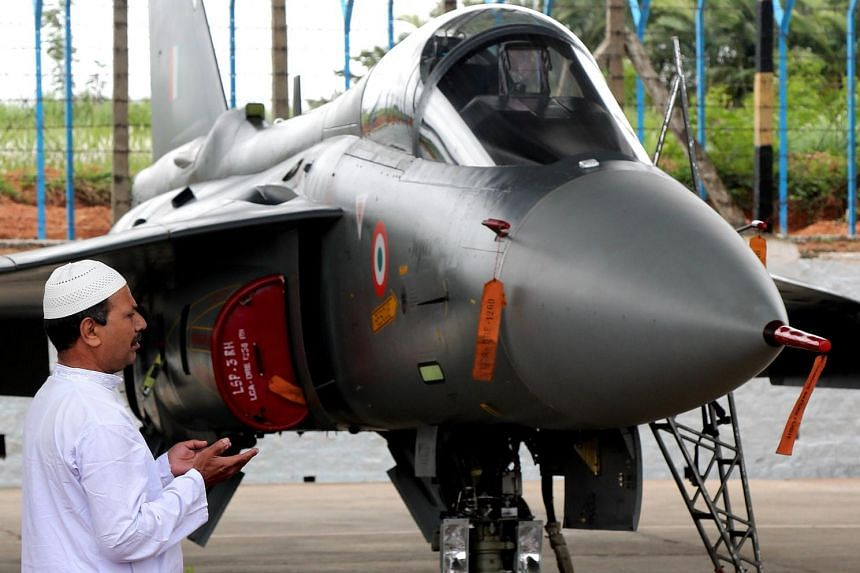 "An Indian Muslim priest prays in front of an Indian Air Force ""Tejas"" Light Combat Aircraft in Bangalore, on July 1, 2016."