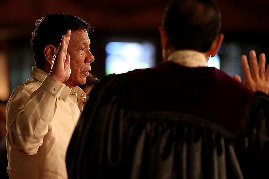 Mr Duterte, in a barong, taking his oath of office as the Philippine President at Malacanang Palace yesterday. The tough-talking, gun-toting former mayor of Davao City won the presidential election in May. Crowds gathering outside the Malacanang Pala